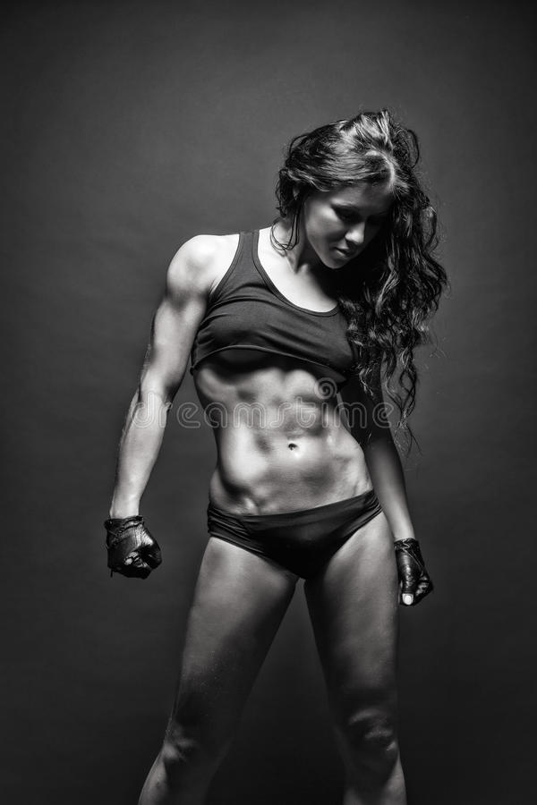 Young muscled fitness brunette girl posing over black background. Fitness woman in sport wear with perfect fitness body royalty free stock photos
