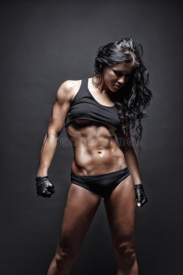 Young muscled fitness brunette girl posing over black background. Fitness woman in sport wear with perfect fitness body royalty free stock photography