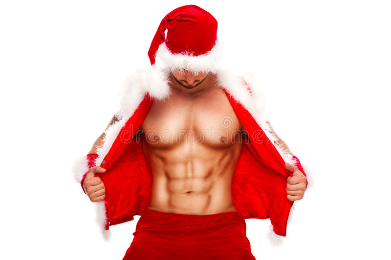 Sexy. Young muscular man wearing Santa hat demonstrate his. Santa. Young muscular man wearing Santa hat demonstrate his muscles. Isolated on white background royalty free stock images