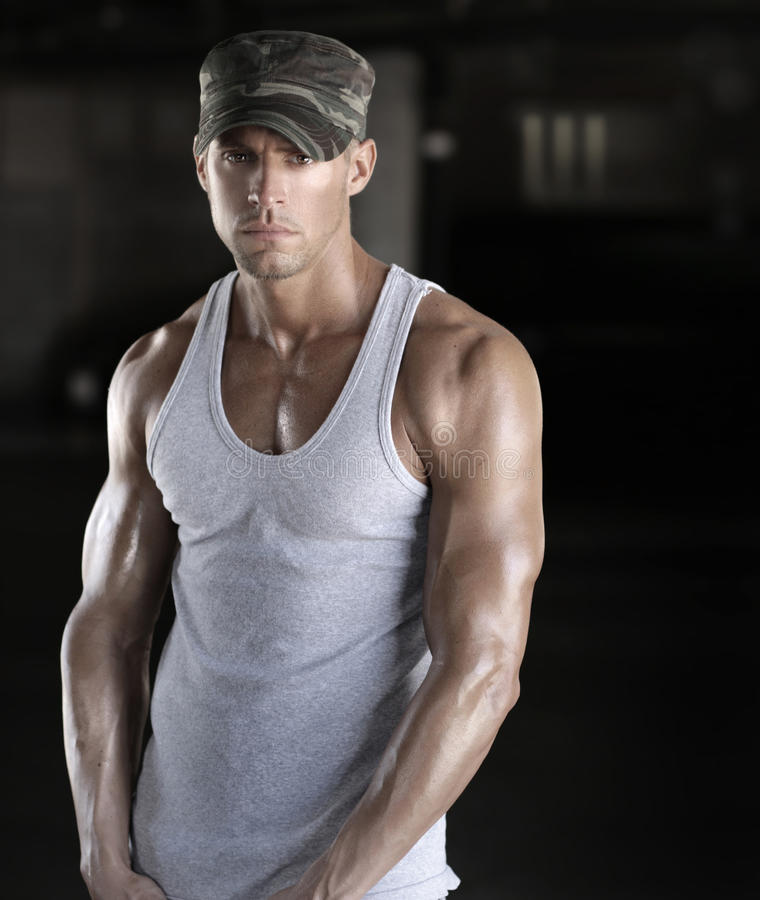 Young soldier. Muscular young soldier man in camo army cap stock photo