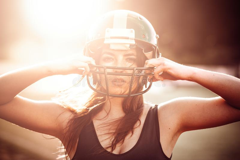 Sexy young sportive girl in uniform of rugby football player in action on the stadium. American football woman player stay on stock photos