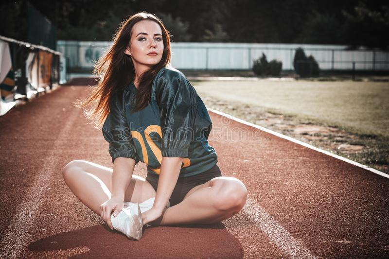 Sexy young sportive girls in t-shirt of rugby football player in action on the stadium. American football woman player sitting on royalty free stock image