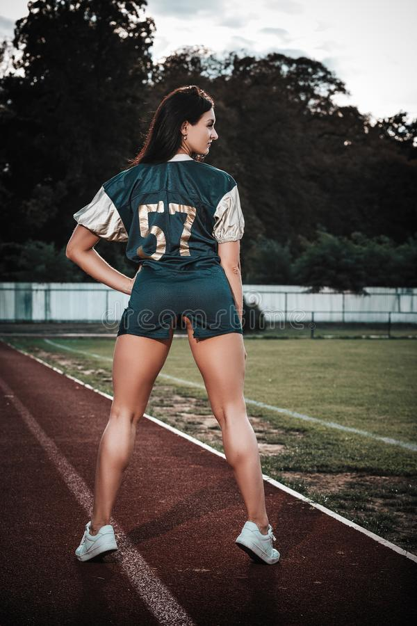 Sexy young sportive girls in t-shirt of rugby football player in action on the stadium. American football woman player stay on royalty free stock photo