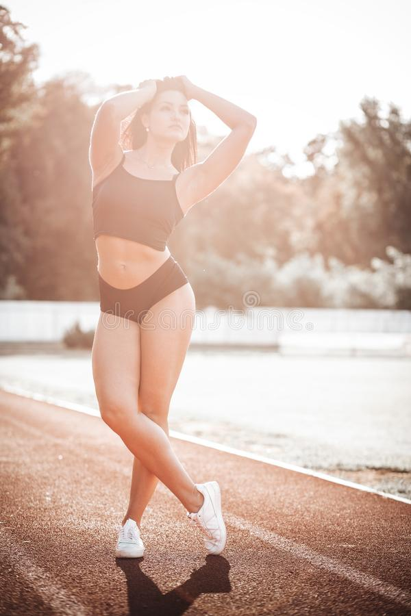 Sexy young sportive girls in t-shirt on the stadium. Fitness woman player on pitch with sunlight royalty free stock image
