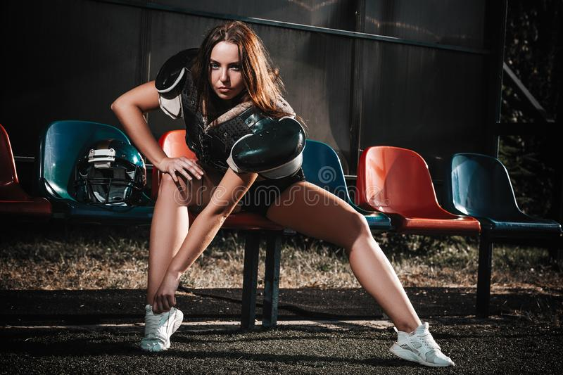 Sexy young sportive girls in uniform of rugby football player in action on the stadium. American football woman player on royalty free stock photos