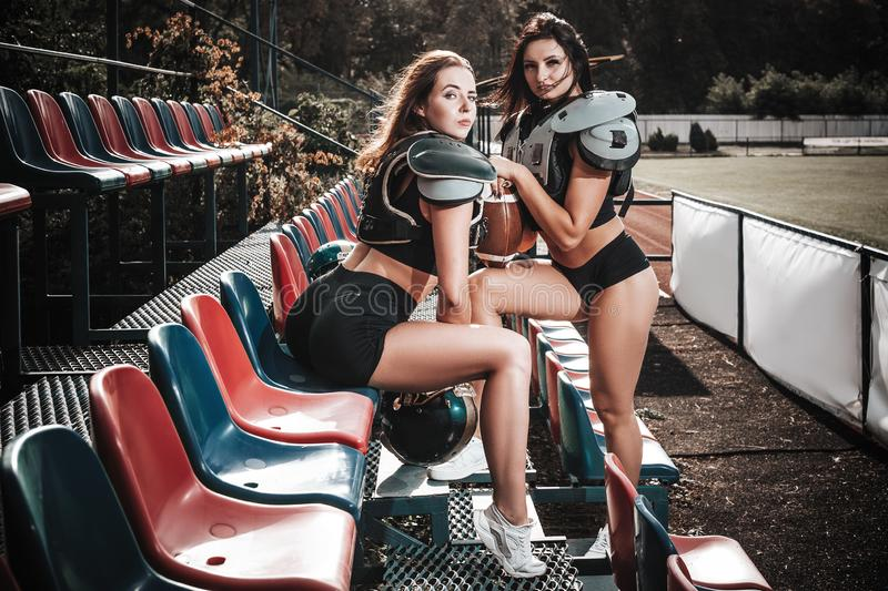 Sexy young sportive girls in uniform of rugby football player in action on the stadium. American football woman players on royalty free stock images