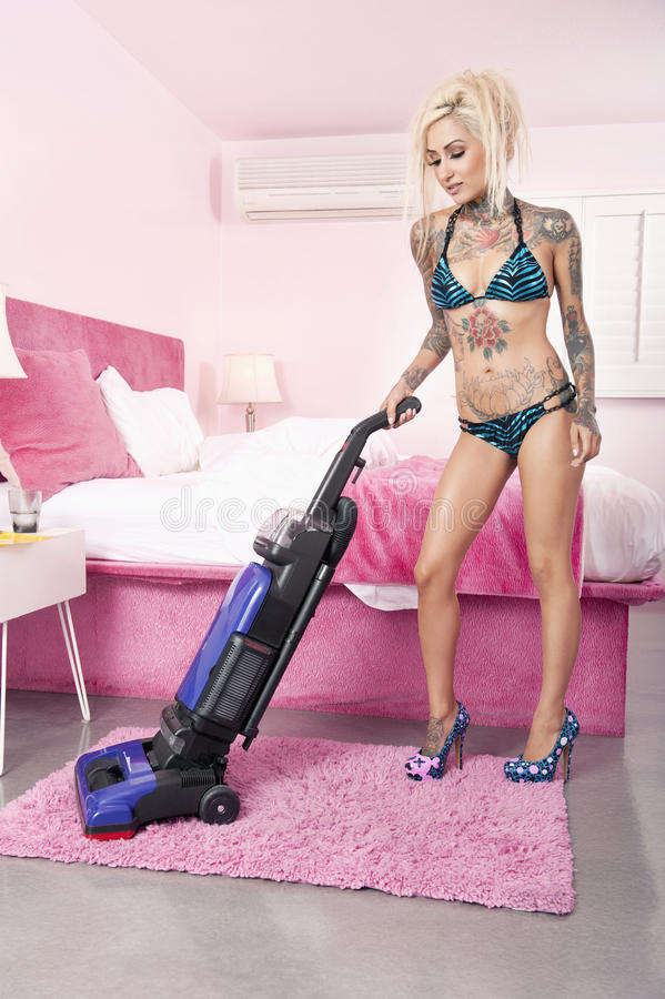 young tattooed woman in bikini vacuuming bedroom royalty free stock photos