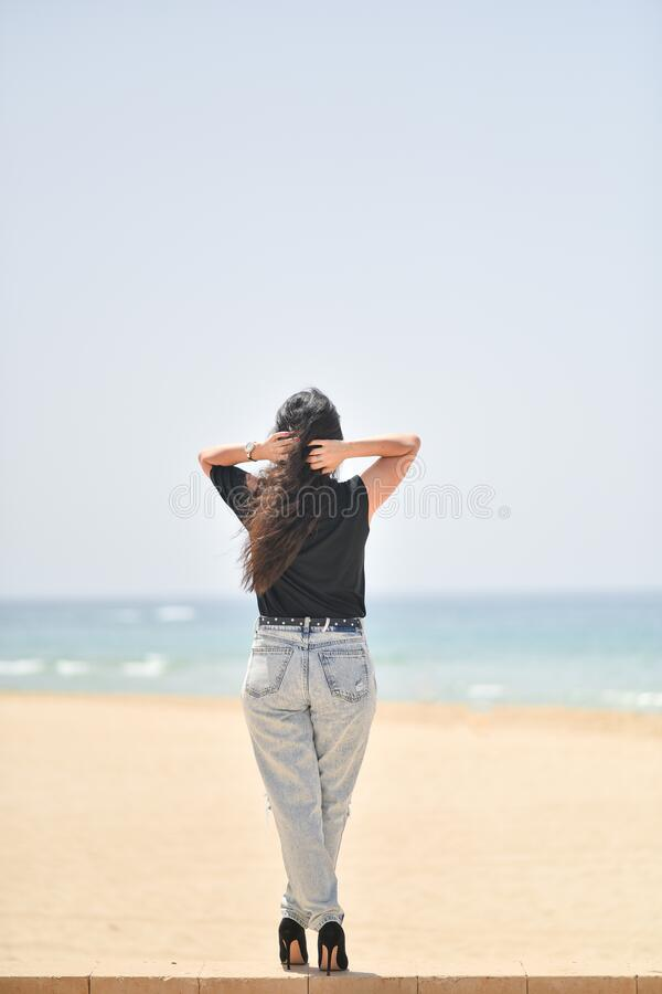 Sexy young woman on black t-shirt, fashion sunglasses and blue jeans stand on the beach, looking at the sea. Girl doing sunbath on. Sexy young woman on black t stock photos