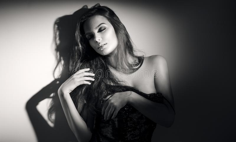 Young woman black and white portrait. Seductive young woman with long hair. Posing in studio stock photo