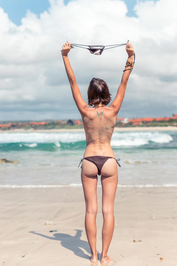 young woman without bra on the tropical beach of Bali island. Bikini girl freedom concept. Indonesia. royalty free stock image
