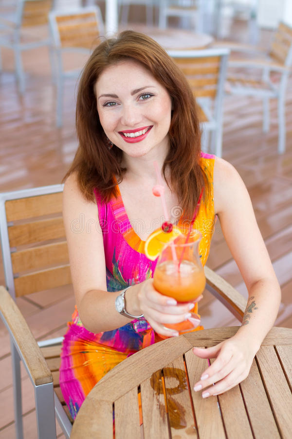 Young woman drinking coctail. Beautiful young lady enjoying her fresh cocktail sitting in a restaurant outdoors stock image
