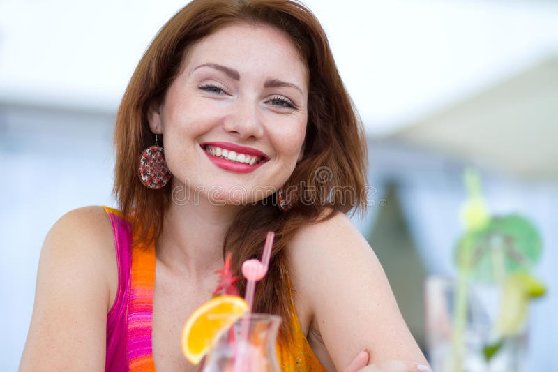 Young woman drinking coctail. Beautiful young lady enjoying her fresh cocktail sitting in a restaurant outdoors royalty free stock image