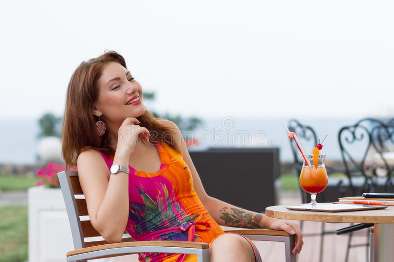 Young woman drinking coctail. Beautiful young lady enjoying her fresh cocktail sitting in a restaurant outdoors stock photography
