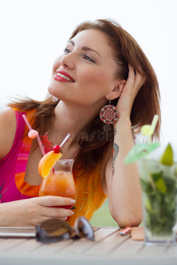 Young woman drinking coctail. Beautiful young lady enjoying her fresh cocktail sitting in a restaurant outdoors stock photo