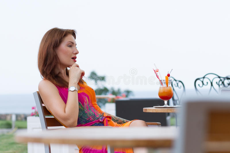 Young woman drinking coctail. Beautiful young lady enjoying her fresh cocktail sitting in a restaurant outdoors royalty free stock photography