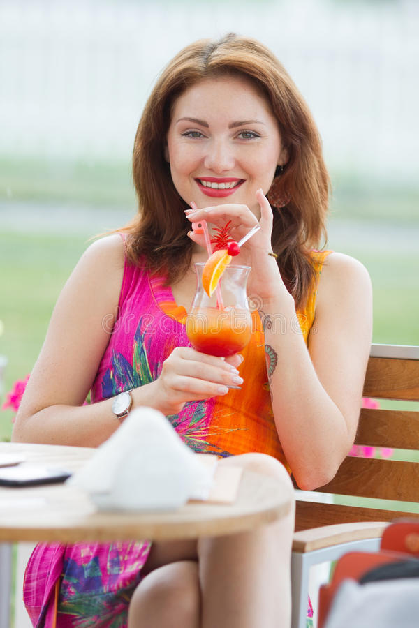 Young woman drinking coctail. Beautiful young lady enjoying her fresh cocktail sitting in a restaurant outdoors royalty free stock photo