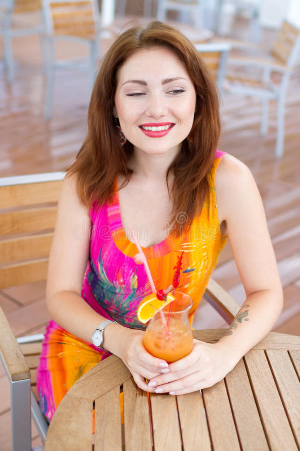 Young woman drinking coctail. Beautiful young lady enjoying her fresh cocktail sitting in a restaurant outdoors stock photos