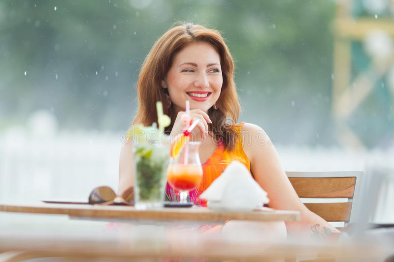 Young woman drinking coctail. Beautiful young lady enjoying her fresh cocktail sitting in a restaurant outdoors royalty free stock photos