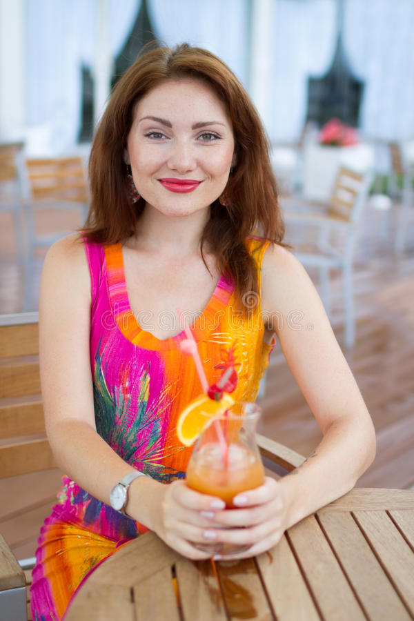 Young woman drinking coctail. Beautiful young lady enjoying her fresh cocktail sitting in a restaurant outdoors royalty free stock images