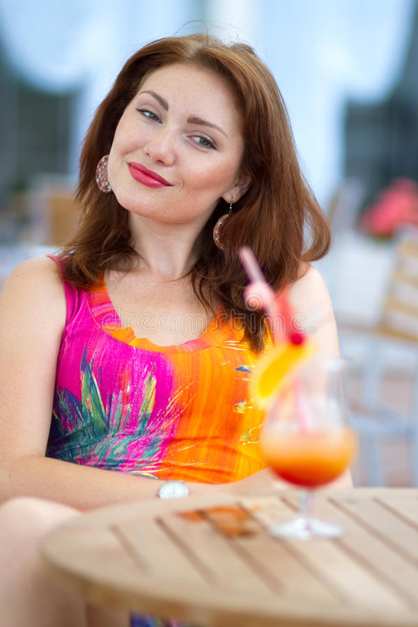 Young woman drinking coctail. Beautiful young lady enjoying her fresh cocktail sitting in a restaurant outdoors stock images