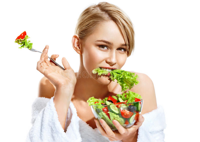 Young woman eating healthy vegetable salad. Photo of attractive lady of the european appearance isolated on white background. Healthy lifestyle royalty free stock photos