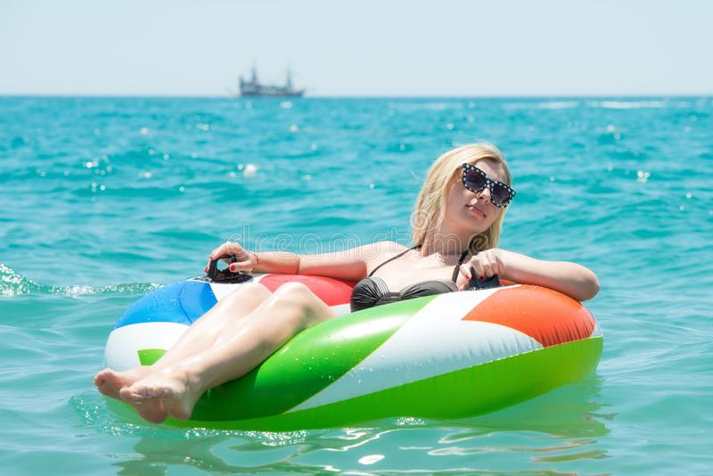 Young woman floating in a rubber ring in the sea. Sexy young woman royalty free stock images