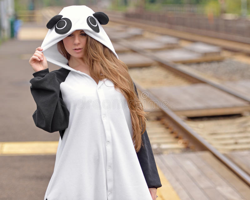 Young woman in fun panda costume. Photo of a beautiful young brunette woman standing at train station or platform wearing a bright panda bear costume stock photos