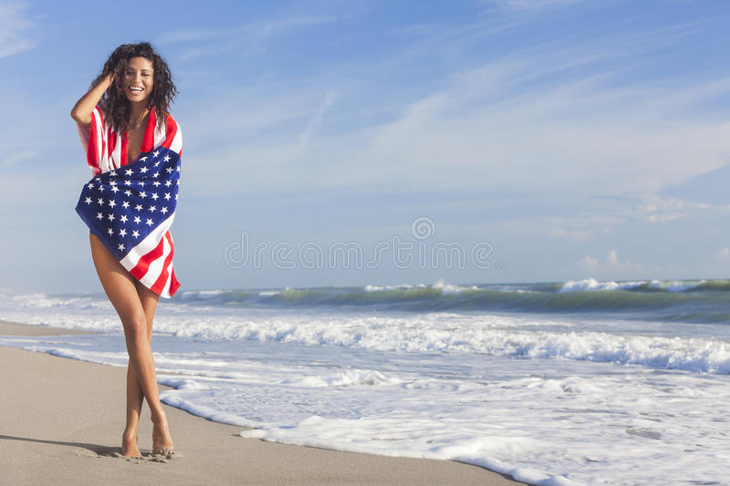 Young Woman Girl in American Flag on Beach. Beautiful young woman laughing wearing bikini and wrapped in American flag towel on a sunny beach stock photo
