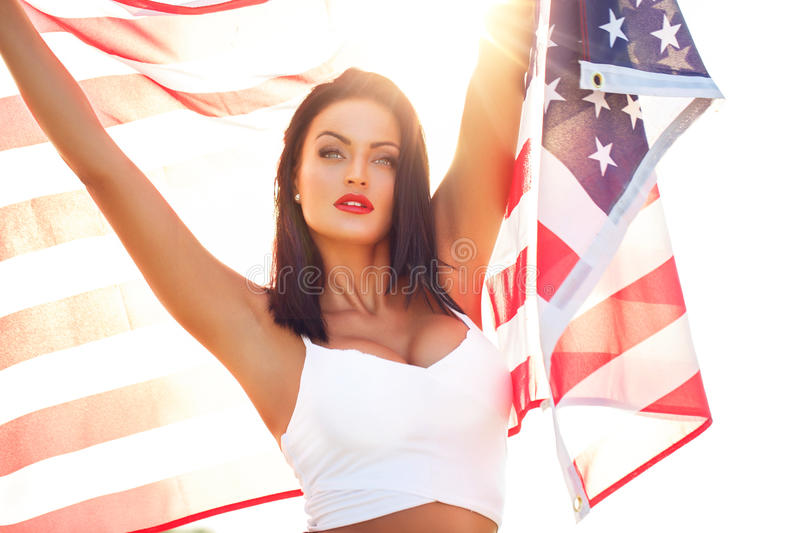 Young woman holding USA flag. Young woman holding star spangled banner USA flag, 4th of July, Independence day stock photos