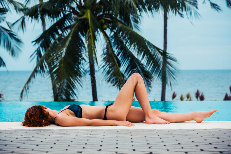 young woman lying by swimming pool royalty free stock image
