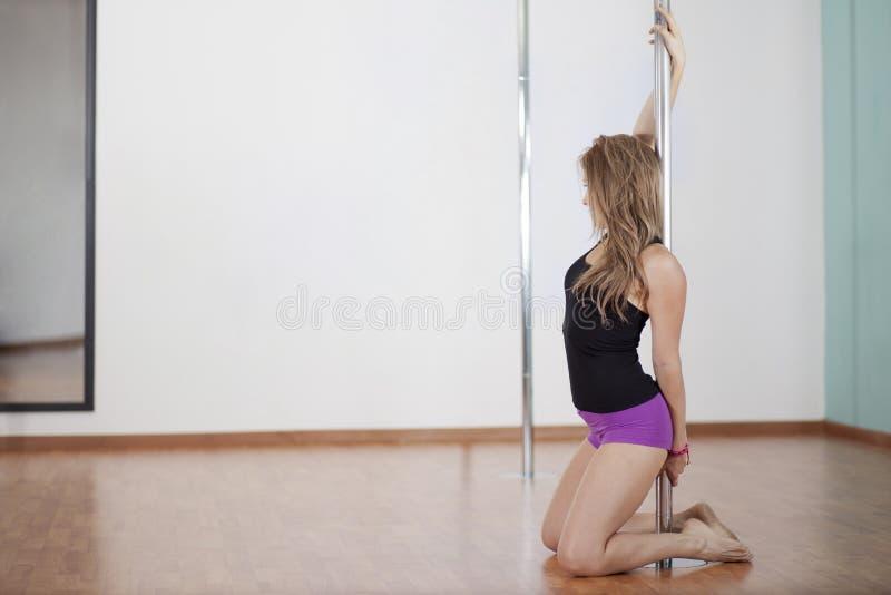 young woman pole dancing stock image