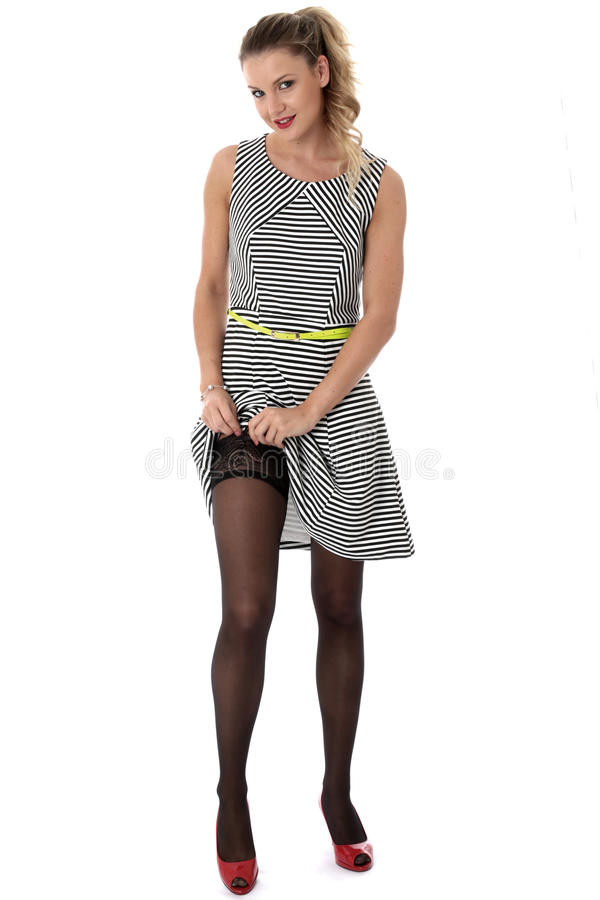 Young Woman Raising Skirt Adjusting Stocking Tops stock images