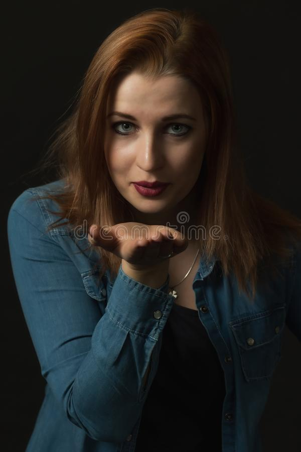 Sexy young woman sending a kiss. Vertically. Low key portrait of sexy young woman sending a kiss with a palm supporting her chin on the black background royalty free stock photo