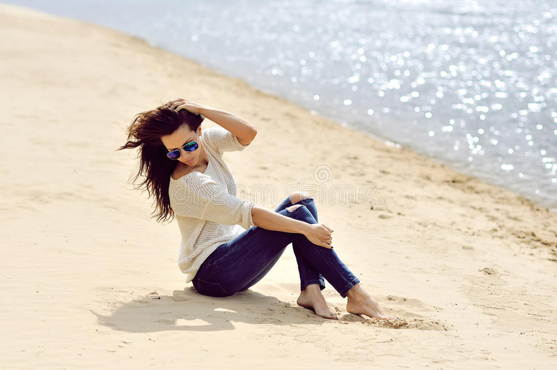 Young woman sitting on a beach outdoor fashion portrait.  royalty free stock photo