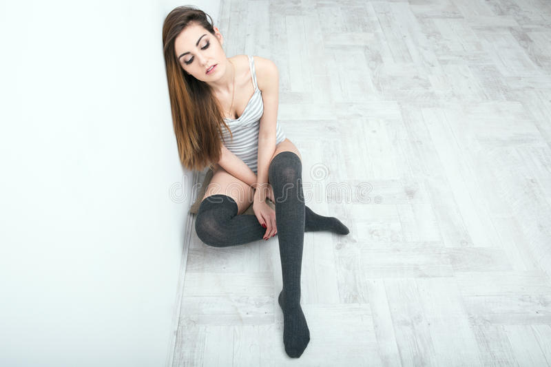 young woman sitting on the floor stock images