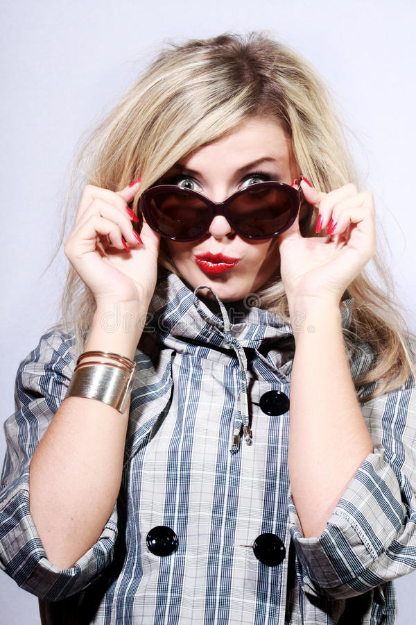 Young woman in sunglasses. Young woman with a bracelet in sunglasses and a coat stock photography