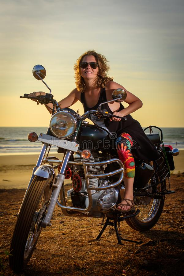 A sexy young woman in sunglasses sits on a black chrome motorbike. Hipster girl on a motorcycle against the sunset. Vertical stock image