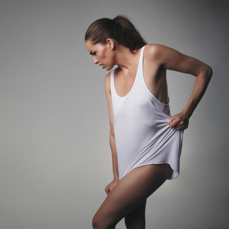 Young woman wearing a tank top. Posing on grey background. Caucasian female model looking down stock photos