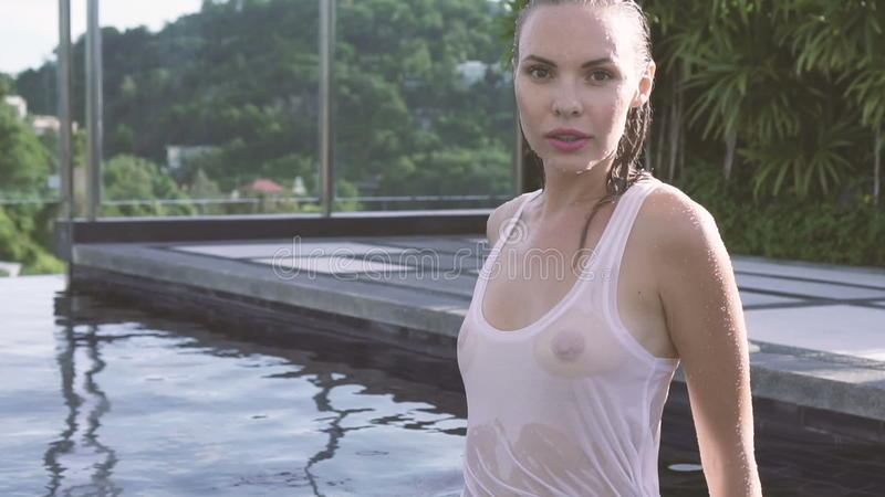 4952993aca Young Woman Wearing White See-through Tank Top With Wet Hair Looking At  Camera Walking In Rooftop Swimming Pool. Stock Footage - Video of female,  ...