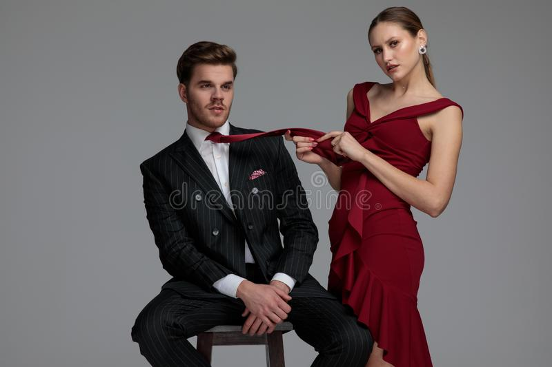 Young woman playing with her man`s tie. Young women playing with her man`s tie on grey studio background royalty free stock photography