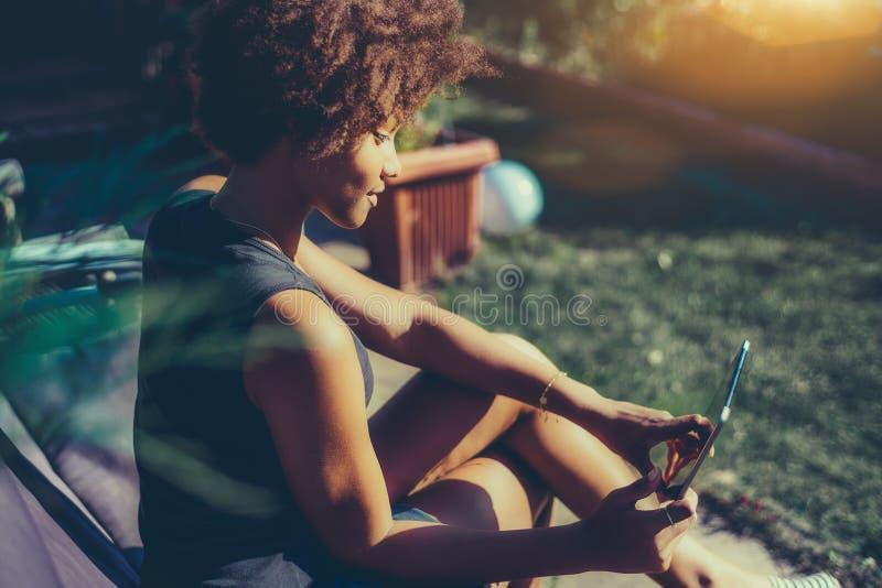 Sexy zwart krullend meisje met digitale tablet in park royalty-vrije stock afbeelding