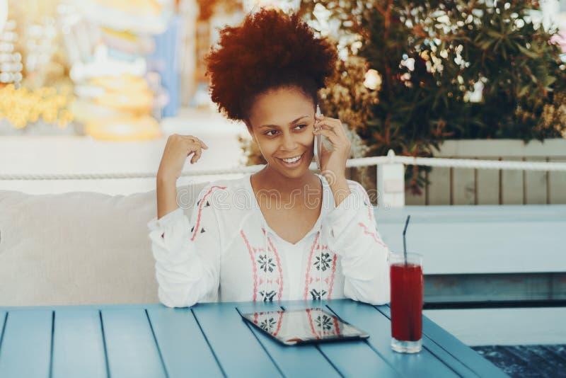 Sexy zwarte dame met smartphone in koffie openlucht royalty-vrije stock foto