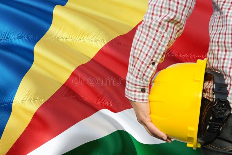 Seychellois inżynier trzyma żółtego zbawczego hełm z machać Seychelles chorągwianego tło Budowy i budynku poj?cie obrazy stock