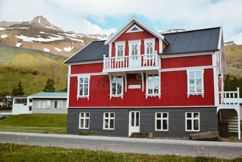 SEYDISFJORDUR, ISLAND, AM 24. JUNI 2013: Buntes rotes Haus in Ost-Island am bewölkten Sommertag mit grauem Dach lizenzfreies stockbild