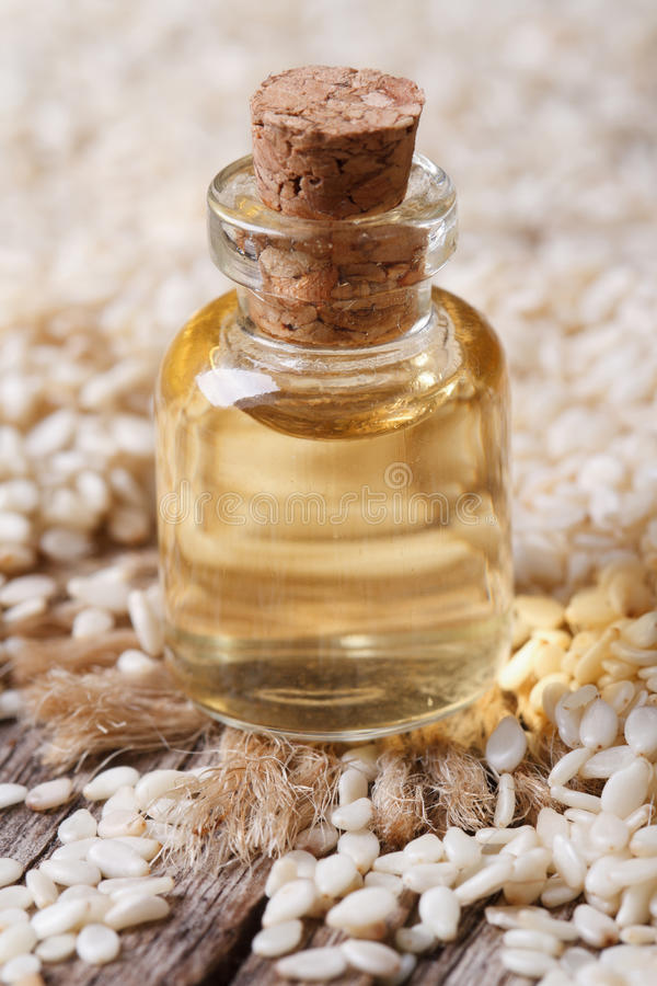 Sezamowy nasieniodajny olej w szklanej butelki zbliżenia vertical zdjęcia royalty free
