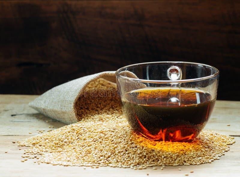 Sezamowy olej w jeden gleass na drewno stole obrazy stock