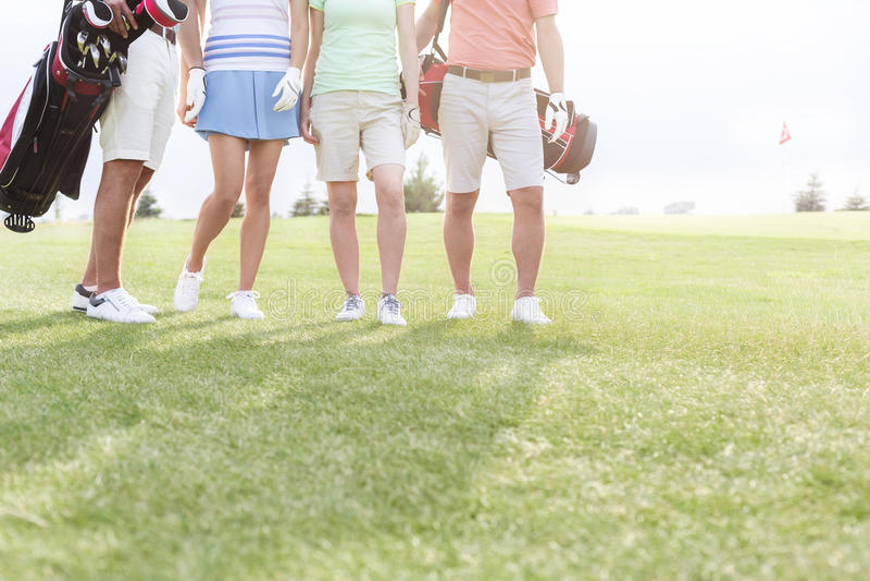 Sezione bassa degli amici che stanno al campo da golf fotografia stock