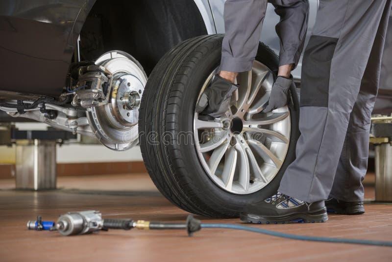 Sezione bassa del meccanico maschio che ripara la gomma dell'automobile nell'officina riparazioni fotografia stock libera da diritti