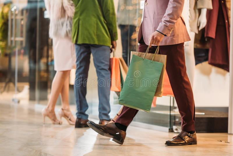sezione bassa dell'uomo alla moda con le coppie di camminata del ND dei sacchetti della spesa che stanno dietro nel centro commer fotografie stock