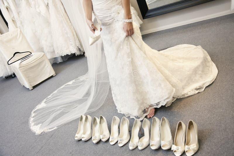 Sezione bassa della giovane donna che sta con la varietà di calzature in boutique nuziale fotografia stock